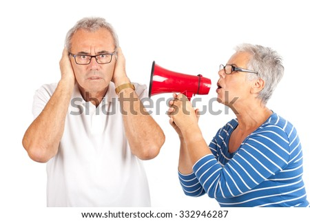 senior couple, woman shouting at the man with megaphone isolated on white - stock photo
