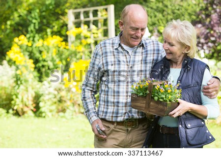 Senior Couple Working In Garden Together - stock photo
