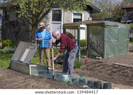 Senior couple working in own allotment garden and preparing the vegetable patch.  - stock photo