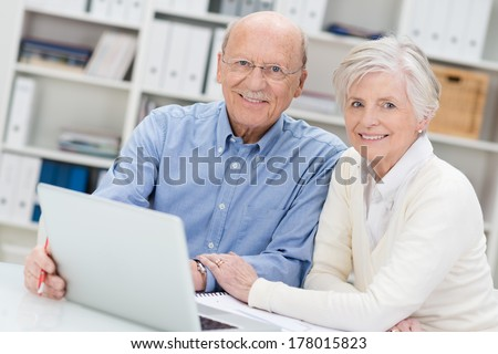Senior couple working on a laptop in an office sitting close together as they share the screen and catch up on social media contacts - stock photo