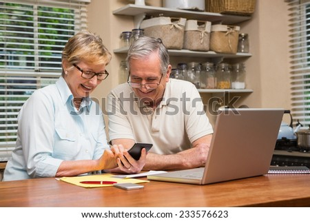 Senior couple working out their bills at home in the kitchen - stock photo