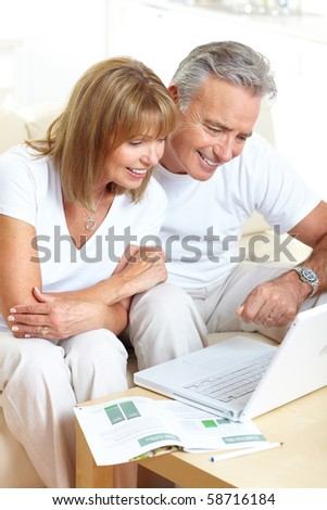 Senior couple  working with laptop at home - stock photo