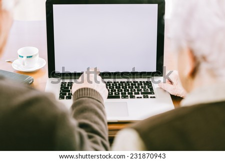 Senior couple working with Laptop, focus on screen - stock photo