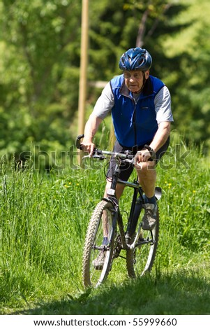 senior cycling with a MTB - stock photo