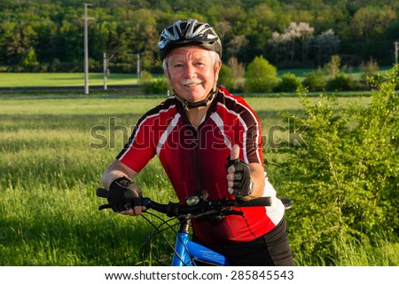 Senior cyclist in the nature liking his sport - stock photo