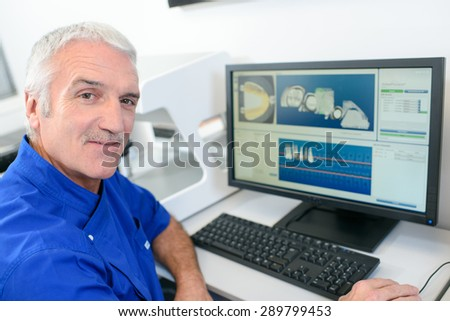 Senior dentist using a computer - stock photo