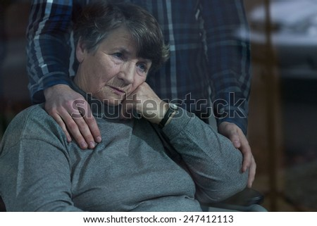 Senior depressed woman and her supportive son - stock photo