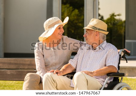 Senior disabled man and wife talking outdoors in park - stock photo