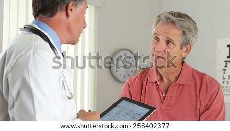 Senior doctor asking elderly patient questions - stock photo