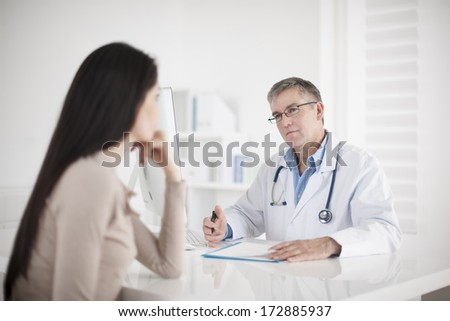 senior  doctor consulting female patient - stock photo