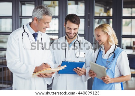 Senior doctor discussing with coworkers at hospital - stock photo