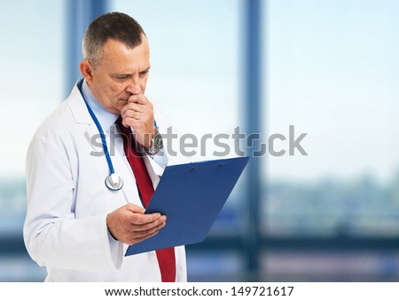 Senior doctor reading a case history - stock photo
