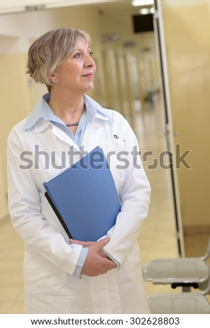 Senior doctor standing in hospital hallway watching outside - stock photo
