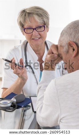 senior doctor talking to her male patient at office - stock photo