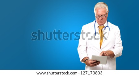 Senior Doctor Using Digital Tablet On Blue Background - stock photo
