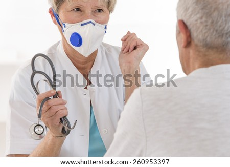 Senior doctor with protective mack in a consultation explaining something to her male patient - stock photo