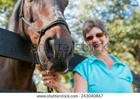 Senior elderly older woman lady smiling and happy playing with brown horse nose leaning over a fence signifying good retirement and health in old age - stock photo
