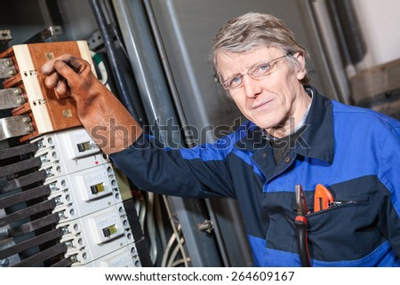 Senior electrical service repairman turning off main switcher in panel - stock photo