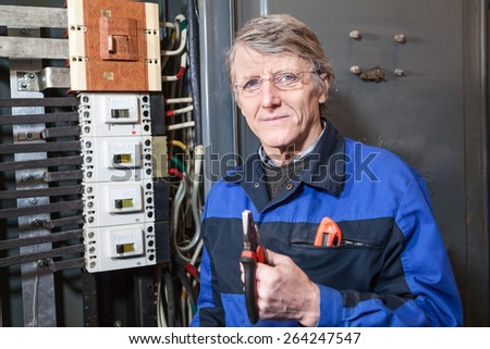 Senior electrician with pliers in his hands standing near high voltage panel - stock photo
