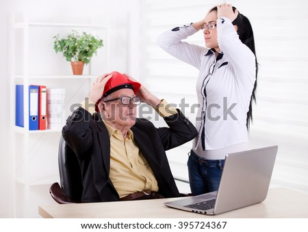 Senior engineer and young assistant having big problem on the project. Both holding head with raised arms in the office - stock photo