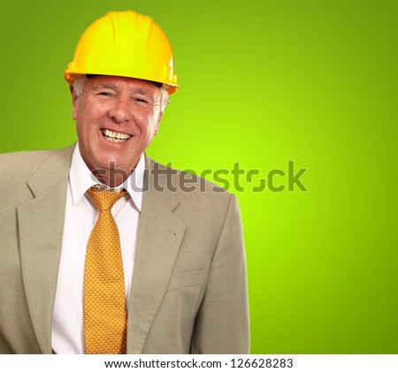 Senior Engineer Standing And Smiling On Green Background - stock photo
