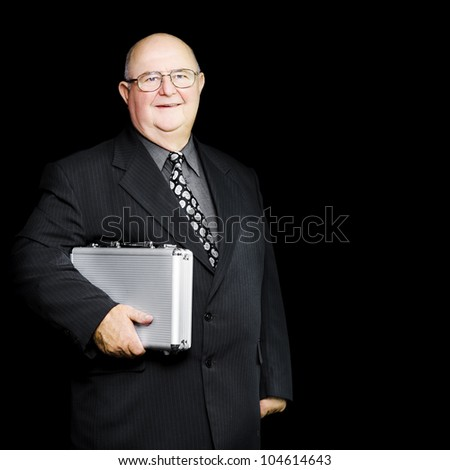 Senior experienced executive clutching his briefcase as he stands waiting for a connection on a business trip in a business travel concept - stock photo