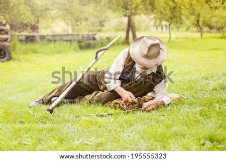 senior farmer using scythe to mow the lawn traditionally - stock photo