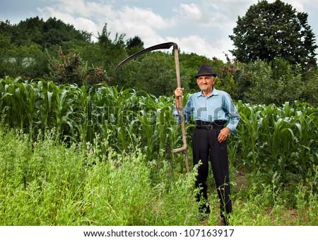 Senior farmer with scythe near a corn field having a break from work - stock photo
