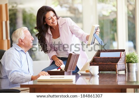 Senior Father Looking At Photo In Frame With Adult Daughter - stock photo