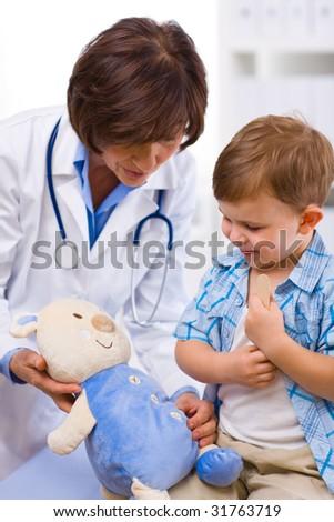 Senior female doctor and happy child examining teddy bear. - stock photo