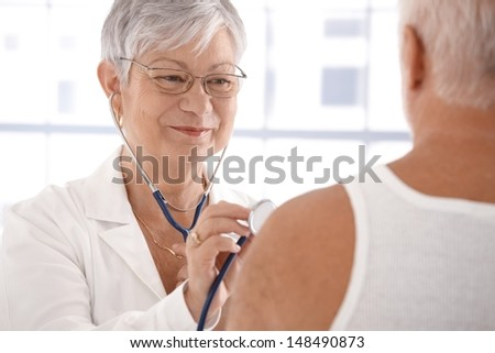 Senior female doctor examining male patient, smiling. - stock photo