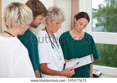 Senior female doctor explaining patient record in hospital - stock photo
