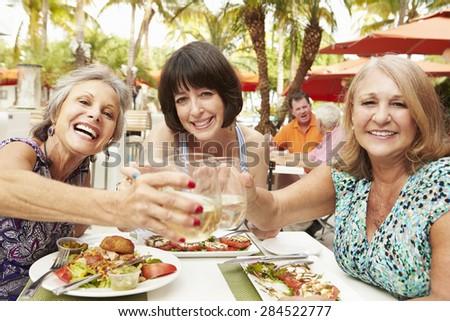 Senior Female Friends Eating Meal In Outdoor Restaurant - stock photo