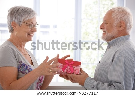 Senior female getting present from husband, smiling.? - stock photo