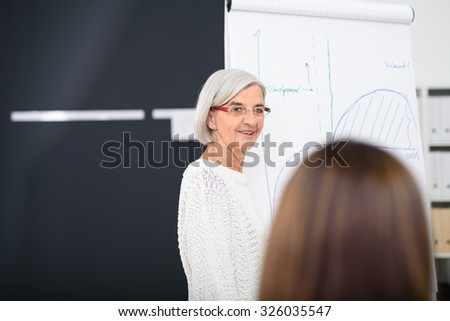 Senior Female Manager Explaining a Graph on a Poster Paper to her Associates In the Office. - stock photo