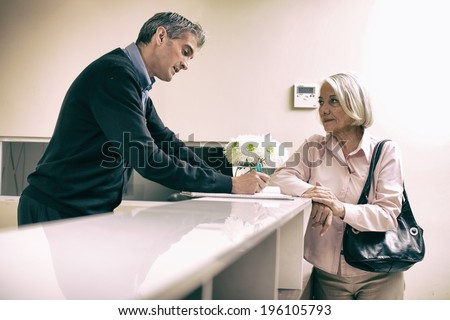Senior female patient at hospital reception desk with man in 40s collecting personal data. - stock photo