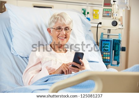 Senior Female Patient In Hospital Bed Using Mobile Phone - stock photo