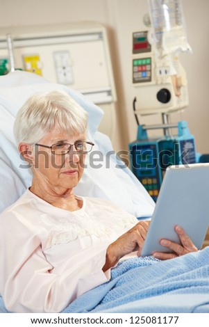 Senior Female Patient Relaxing In Hospital Bed With Digital Tablet - stock photo