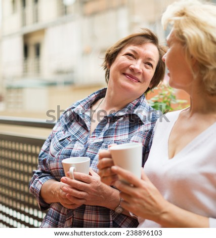 Senior female pensioners relaxing with cup of coffee on balcony - stock photo