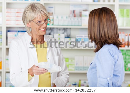 Senior female pharmacist giving prescribed medicine to customer in pharmacy - stock photo
