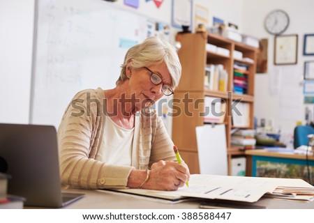 Senior female teacher at her desk marking studentsâ?? work - stock photo