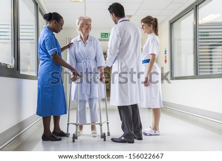 Senior female woman hospital patient in corridor with two female nurses, one African American and Asian male doctor. - stock photo