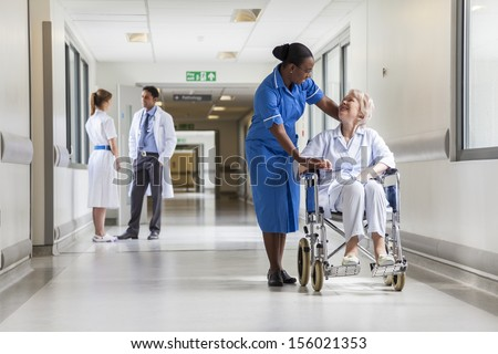 Senior female woman patient in wheelchair sitting in hospital corridor with African American female nurse and doctor - stock photo