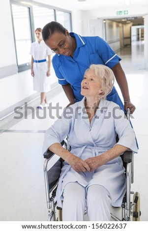 Senior female woman patient in wheelchair sitting in hospital corridor with African American female nurse - stock photo