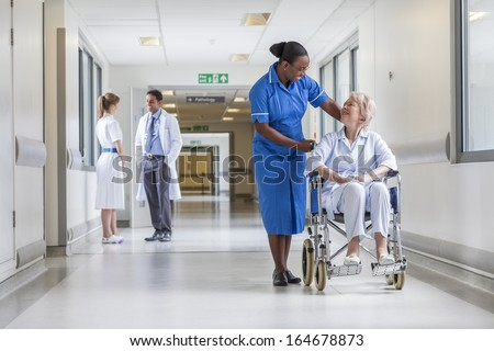 Senior female woman patient in wheelchair sitting in hospital corridor with African American female nurse doctor and nurse in background - stock photo