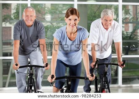 Senior fitness class in gym doing bike exercises - stock photo
