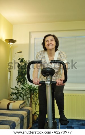 Senior fitness woman exercise on spinning bicycle at home - stock photo