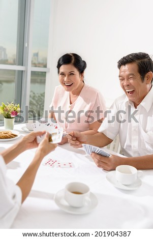 Senior friends playing cards indoors - stock photo