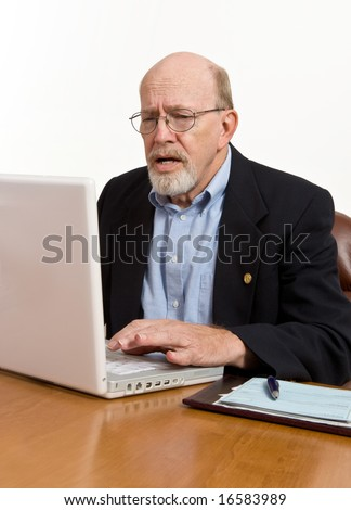 Senior frustrated with his laptop computer and the entire digital world. - stock photo