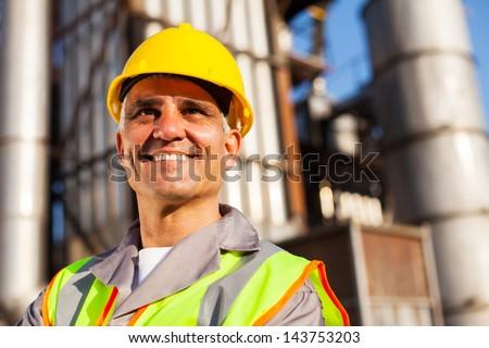 senior fuel refinery worker closeup portrait inside plant - stock photo